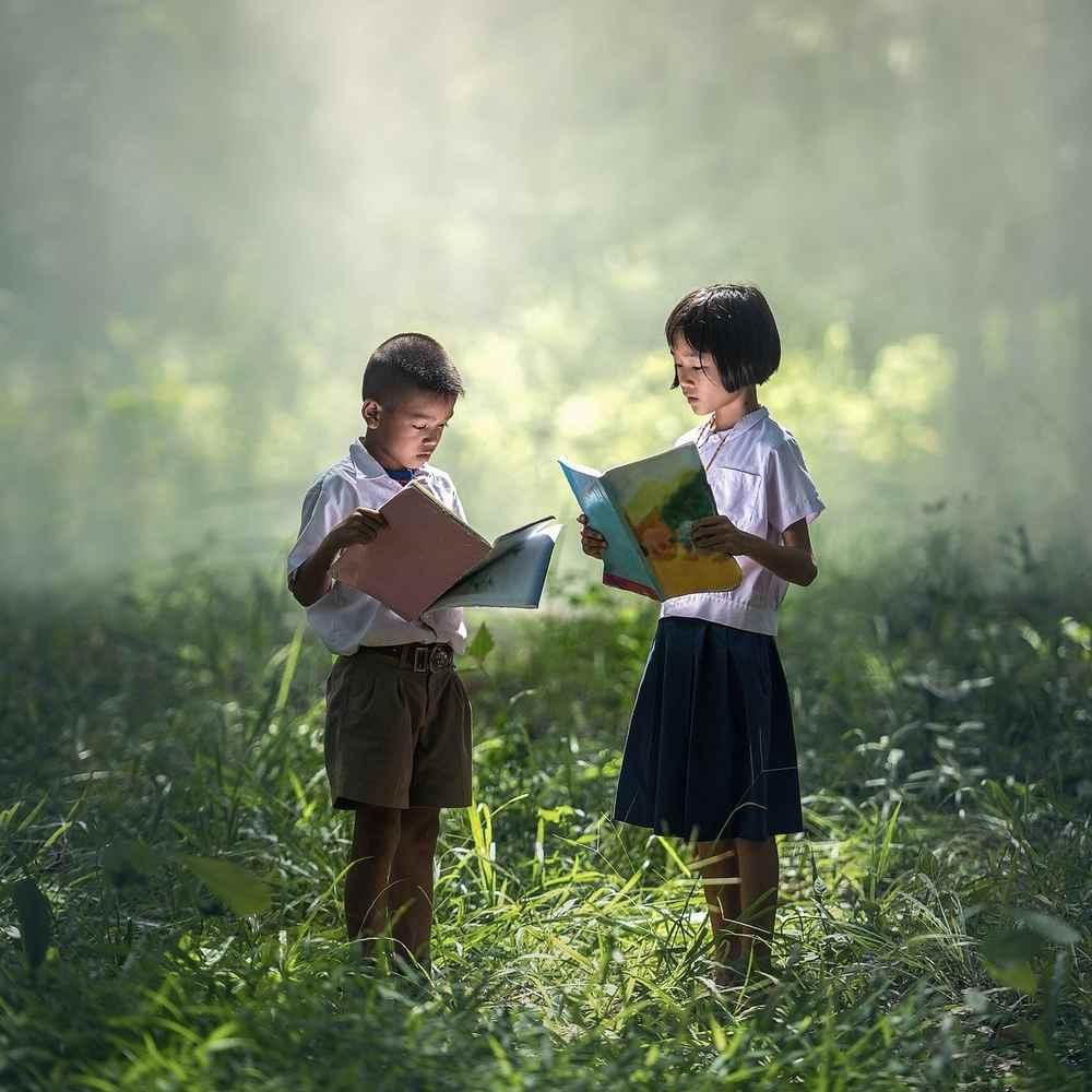 Enfants qui lisent dans l'herbe pour représenter le travail à deux